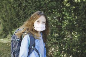 Schülerin auf dem Weg zum Schulbus mit Maske aufgrund der Corona-Pandemie. Foto: © AdobeStock.com/epixproductions